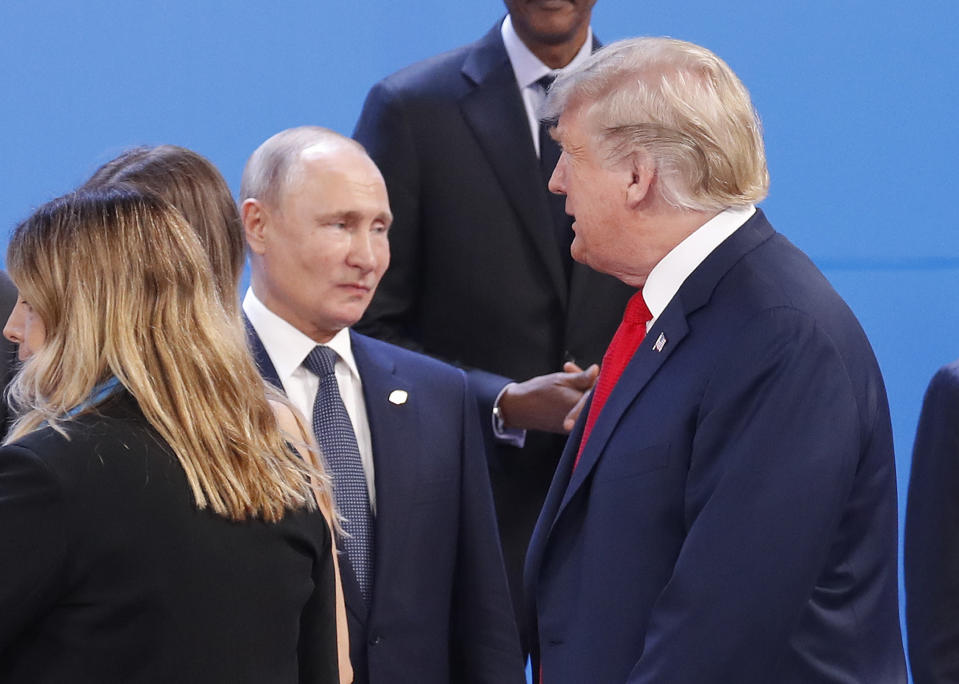 FILE - In this Nov. 30, 2018, file photo, President Donald Trump, right, walk past Russia's President Vladimir Putin, left, as they gather for the group photo at the start of the G20 summit in Buenos Aires, Argentina. For the past three years, the administration has careered between President Donald Trump's attempts to curry favor and friendship with Vladimir Putin and longstanding deep-seated concerns about Putin's intentions. (AP Photo/Pablo Martinez Monsivais, File)