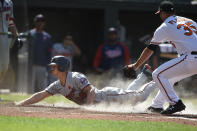 Minnesota Twins' Rob Refsnyder, left, slides across the plate as Baltimore Orioles pitcher Adam Plutko covers in the 10th inning of a baseball game Monday, May 31, 2021, in Baltimore. Refsnyder was safe, scoring the go-ahead run on a wild pitch. (AP Photo/Gail Burton)