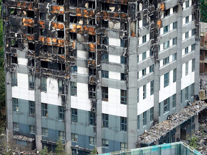 Remains of the tower's unburned lower floors, with untouched cladding still in place, are pictured on 22 June 2017 – eight days after the fire (AFP via Getty Images)