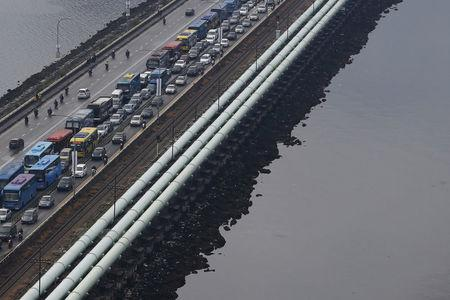 FILE PHOTO: Water pipes run the length of the causeway between Singapore and Malaysia's southern city of Johor Bahru (R), transporting up to 250 million gallons (946 million litres) of water or approximately 60 percent of Singapore's water needs each day, March 10, 2016.   REUTERS/Edgar Su/File Photo