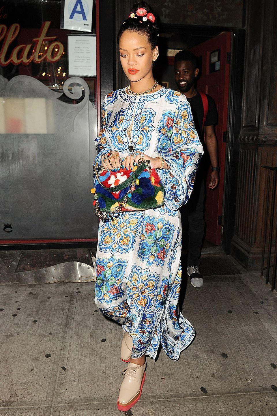 <p>In a Dolce & Gabbana caftan, printed handbag and platform oxfords, topped with some floral accents in her hair</p>