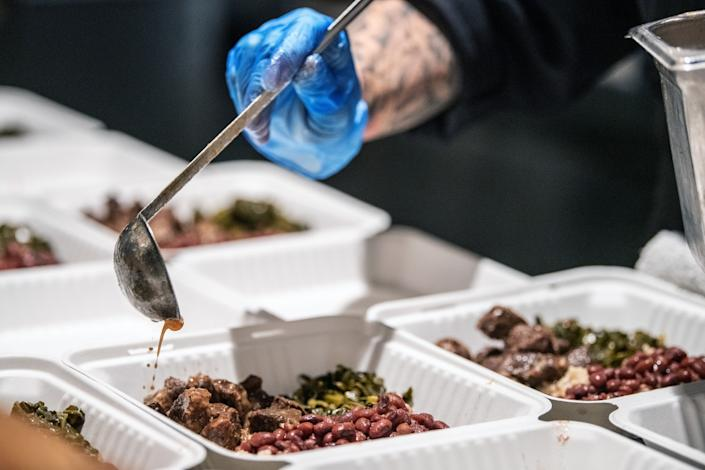 """Meals are available on a sliding scale and range from $20 to $0 depending on what an individual can pay. Alta Adams is offering the """"family meal,"""" which consists of braised beef, red beans, brown rice and collard greens. <span class=""""copyright"""">(Mariah Tauger / Los Angeles Times)</span>"""