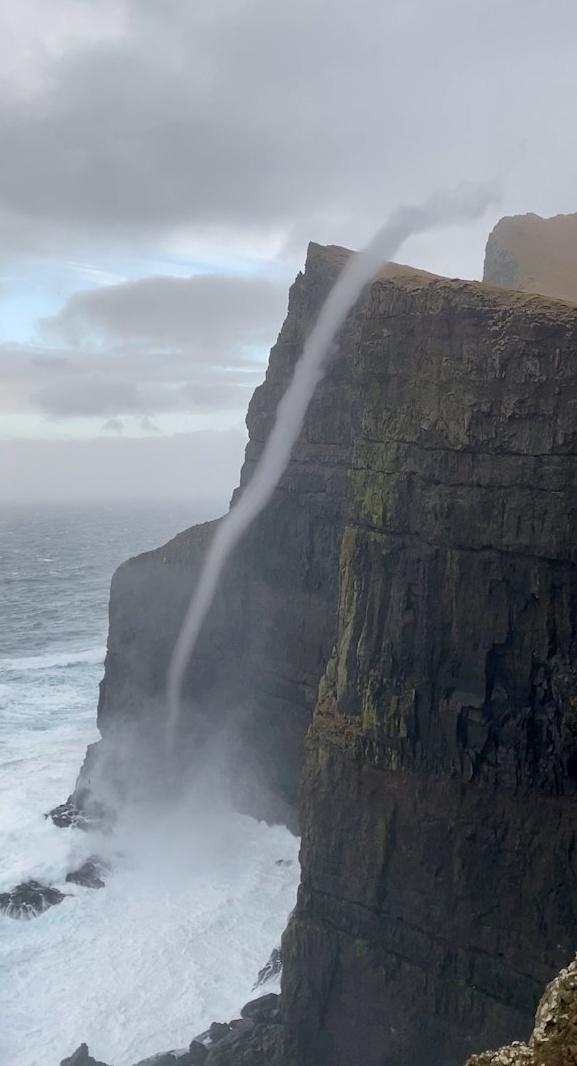 Video grab from the amazing footage of water flowing upwards on the  cliffs off Suðuroy in the Faroe Islands - a phenomenon known as a water spout. See SWNS story SWOCvortex. This is the incredible moment water flowed UPWARDS - after waves were caught in a rare sea vortex. Samy Jacobsen, 41, was out walking along the cliffs off Suðuroy in the Faroe Islands when he spotted a whirlwind of water rising from the waves. He watched as the vortex of spray climbed up the side of the 470m sea cliff - known as Beinisvørð - and billowing on to the cliff top, on Monday. Weather experts said it was a water spout - a spiralling pillar of air - which forms like a tornado over the water when a cliff edge spins the wind in a circle.