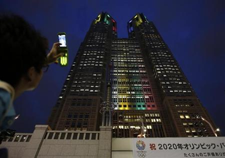 Visitor takes photos of Tokyo Metropolitan Government Building illuminated in the Olympic colors in Tokyo