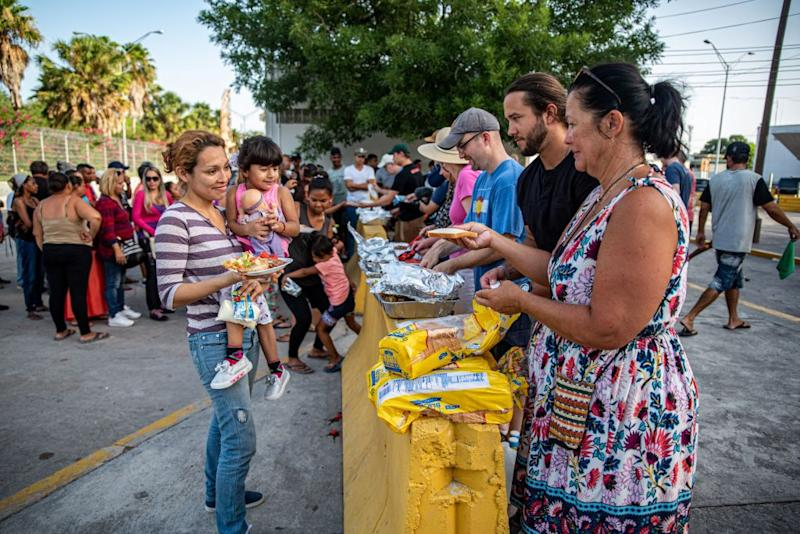 Volunteers hand out food to migrants near the Mexican border in Matamoros, Tamaulipas on June 29, 2019. | Sergio Flores—AFP/Getty Images