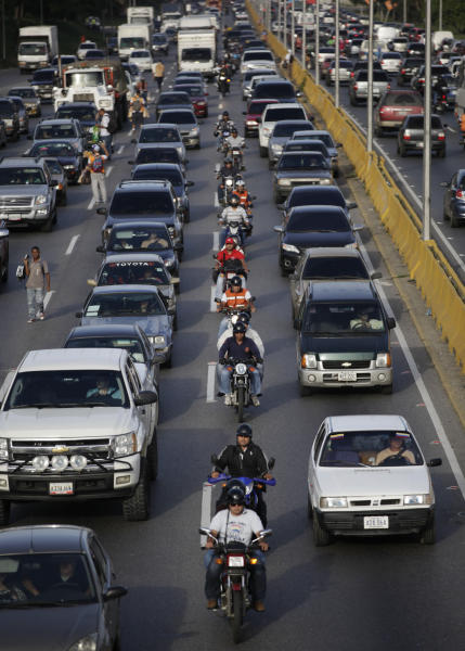 In this photo taken Friday, June 21, 2013, motorcyclists ride in a single file between traffic lanes in Caracas, Venezuela. Transportation infrastructure has been neglected for decades leading to traffic congestion so bad that Caracas is almost always best navigated on motorcycle. A two-hour car drive to work can take less than half an hour on the back of a bike. (AP Photo/Ariana Cubillos)
