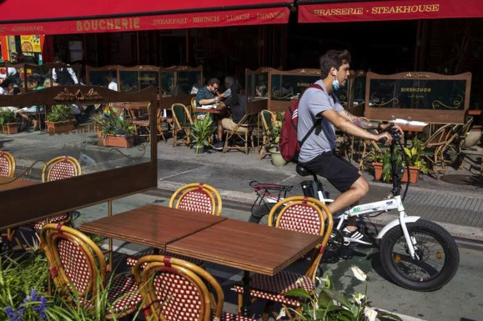 A man on a bike rides past customers social distancing in outdoor seating at a restaurant in New York City
