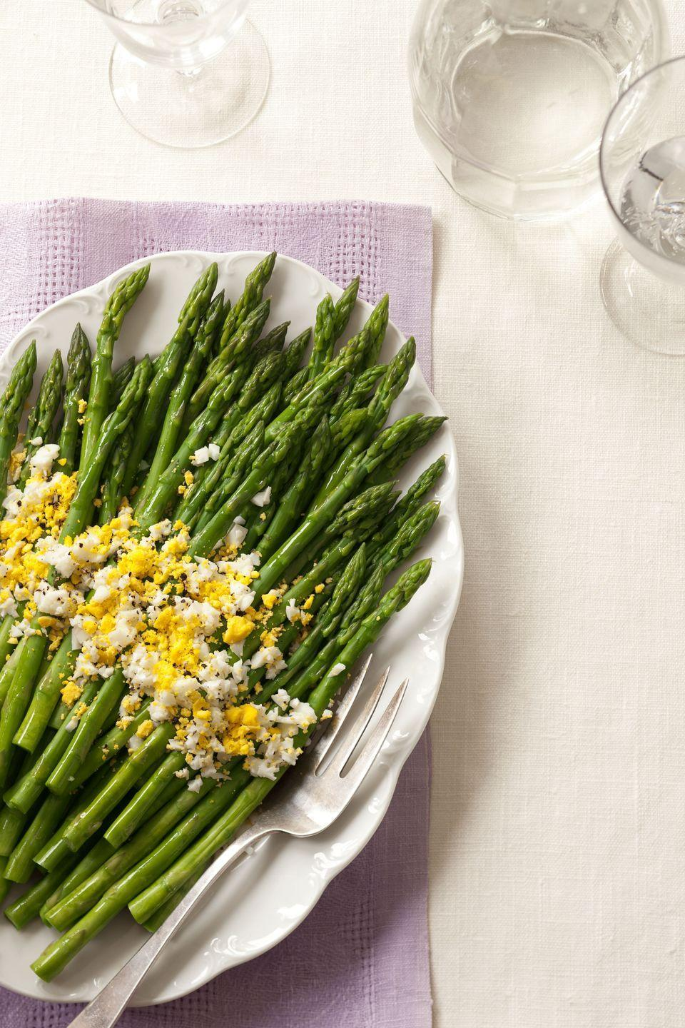 """<p>Bright green asparagus gets fancied up with a shower of grated egg and lemon zest to create springtime on a plate. You can prepare the asparagus, dressing, and eggs ahead of time — just dress at the last minute to keep the colors vibrant.</p><p><em><em><a href=""""https://www.goodhousekeeping.com/food-recipes/a14410/asparagus-eggs-mimosa-recipe-ghk0413/"""" rel=""""nofollow noopener"""" target=""""_blank"""" data-ylk=""""slk:Get the recipe for Asparagus With Eggs Mimosa"""" class=""""link rapid-noclick-resp"""">Get the recipe for Asparagus With Eggs Mimosa </a><em><em><a href=""""https://www.goodhousekeeping.com/food-recipes/a14410/asparagus-eggs-mimosa-recipe-ghk0413/"""" rel=""""nofollow noopener"""" target=""""_blank"""" data-ylk=""""slk:»"""" class=""""link rapid-noclick-resp"""">»</a></em></em></em></em></p>"""