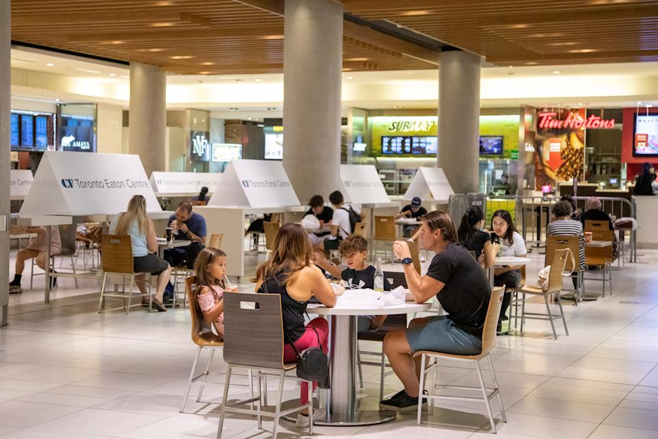 People eat in the foodcourt at the Eaton Centre shopping centre after indoor dining restaurants, gyms and cinemas re-open under Phase 3 rules from coronavirus disease (COVID-19) restrictions in Toronto, Ontario, Canada July 31, 2020.  REUTERS/Carlos Osorio