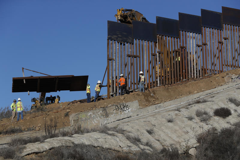 Workers add new sections to the U.S. border wall in Tijuana, Mexico, on Saturday