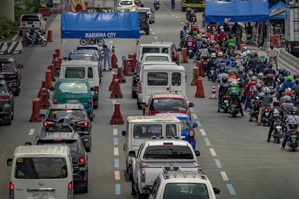 Motorists queue at a quarantine checkpoint, after the government relaxed lockdown measures and allowed work to resume in more industries on May 18, 2020 in Marikina, Metro Manila, Philippines. (Photo by Ezra Acayan/Getty Images)