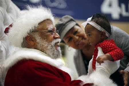African American Santa Claus Langston Patterson (L), 77, greets four-month-old Raelyn Price as her grandmother Gloria Boissiere looks on, at Baldwin Hills Crenshaw Plaza mall in Los Angeles, California, December 16, 2013. REUTERS/Lucy Nicholson