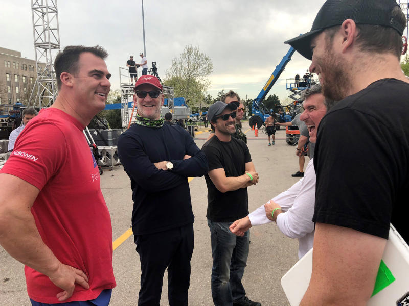"This Wednesday, April 10, 2019 photo Oklahoma's new Republican Gov. Kevin Stitt, left, talks on the set of ""American Ninja Warrior"" outside the state Capitol in Oklahoma City, Okal., after trying out the obstacle course. Organizers of the reality television show that features high-level athletes racing through grueling obstacles say the 47-year-old ex-CEO is the first governor to give the course a try. Stitt bloodied his elbow completing a rope swing to a landing pad after jumping across a pool of water. (Donelle Harder/Office of Governor Kevin Stitt via AP)"