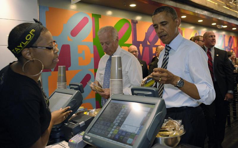 President Barack Obama tries to decide what kind of cookie to get as he and Vice President Joe Biden order lunch at Taylor Gourmet sandwich shop near the White House in Washington, Friday, Oct. 4, 2013. The president and vice president stepped out of the White House on a surprise and rare off-campus stroll to grab lunch at a neighborhood eatery. (AP Photo/Susan Walsh)