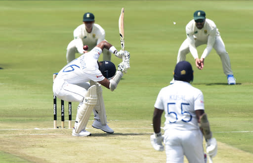 Sri Lanka's Dimuth Karunaratne, centre ducks under a bounce ball, on day one of the first cricket test match between South Africa and Sri Lanka at Super Sport Park Stadium in Pretoria, South Africa, Saturday, Dec. 26, 2020. (AP Photo/Catherine Kotze)