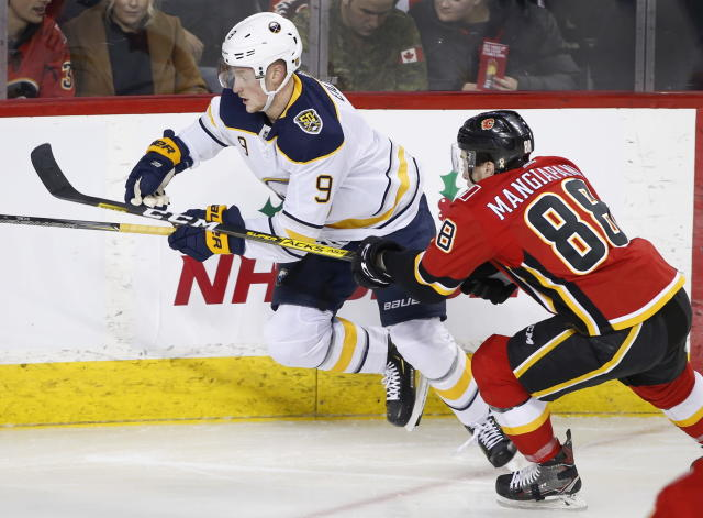 Buffalo Sabres Jack Eichel, left, battles against Calgary Flames player Andrew Mangiapane during the second period of an NHL hockey game Thursday, Dec. 5, 2019, in Calgary, Alberta. (Larry MacDougal/The Canadian Press via AP)