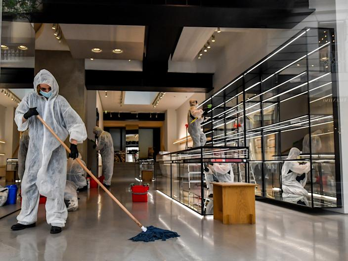 Workers wearing protective outfits sanitize a shop in via Monte Napoleone fashion shopping street, in Milan, Italy, Monday, April 27, 2020.  Italian factories, construction sites and wholesale supply businesses can resume activity as soon as they put safety measures into place aimed at containing contagion with COVID-19. This concession comes with partial easing of national lockdown restrictions announced Sunday night by Italian Premier Giuseppe Conte. (Claudio Furlan/LaPresse via AP)
