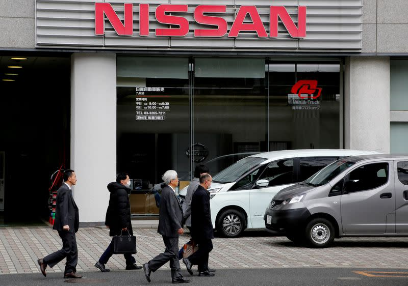 FILE PHOTO: People walk past a dealer shop of Nissan Motor in Tokyo