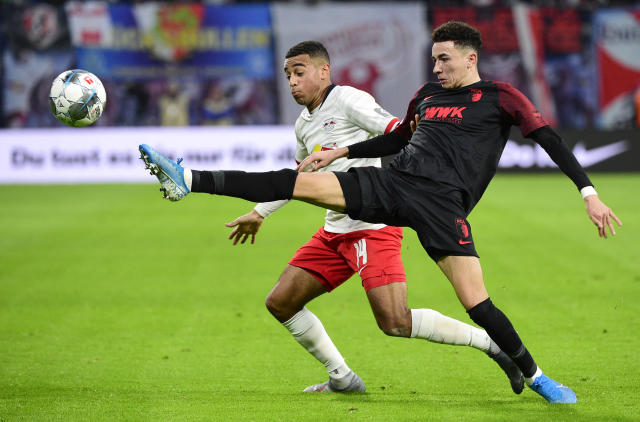 Augsburg's Ruben Vargas, right, and Leipzig's Tyler Adams fight for the ball during the German Bundesliga soccer match between Leipzig and Augsburg at the Red Bull Arena stadium in Leipzig, Germany, Saturday, Dec. 21, 2019. (AP Photo/Jens Meyer)