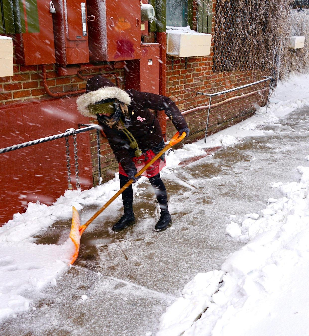 """Head bent against the driving snow, Rindi Gray, 48, shovels the sidewalk outside Denver's """"My Brothers Bar,"""" during the March 13, 2019, blizzard."""