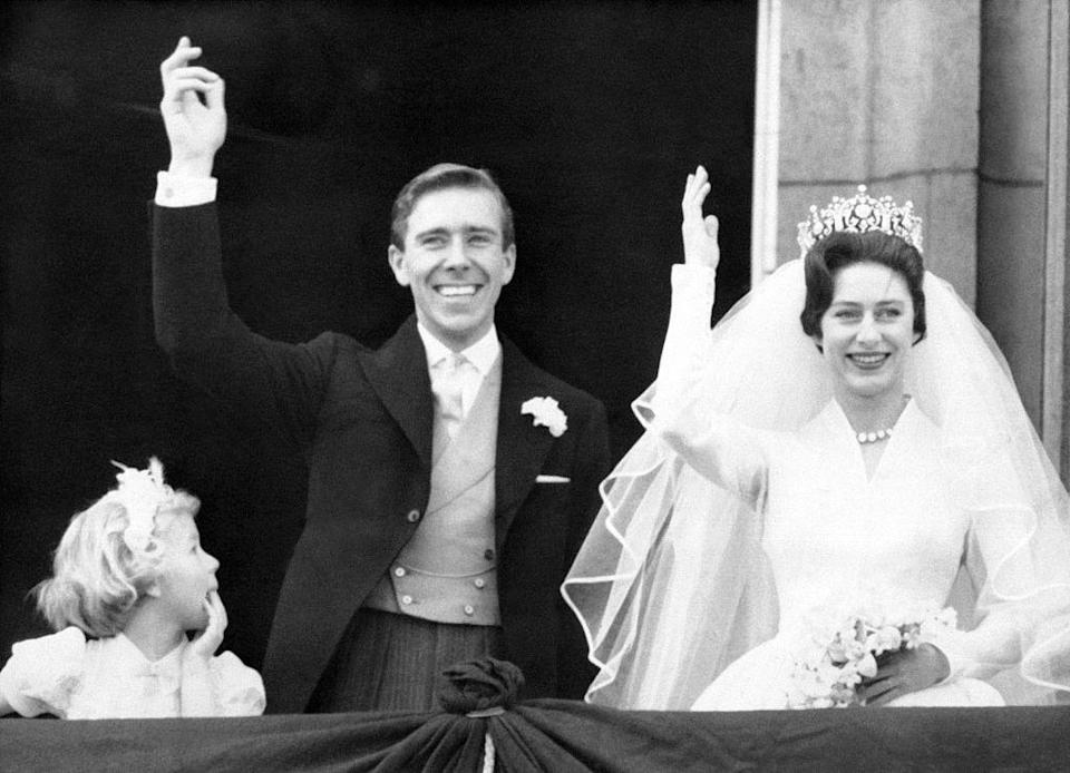 """<p>Princess Margaret and the newly titled <a href=""""https://www.townandcountrymag.com/society/tradition/a29668117/lord-snowdon-antony-armstrong-jones-princess-margaret-husband-facts/"""" rel=""""nofollow noopener"""" target=""""_blank"""" data-ylk=""""slk:Earl of Snowdon"""" class=""""link rapid-noclick-resp"""">Earl of Snowdon</a> wave to well-wishers on the Buckingham Palace balcony after their ceremony at Westminster Abbey. The Princess paired her <a href=""""https://www.brides.com/princess-margaret-wedding-5087739"""" rel=""""nofollow noopener"""" target=""""_blank"""" data-ylk=""""slk:silk organza Norman Hartnell"""" class=""""link rapid-noclick-resp"""">silk organza Norman Hartnell</a> wedding dress with the Poltimore tiara. </p>"""