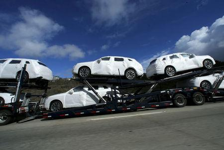 FILE PHOTO: New vehicles covered in protective wrapping are shipped by a transport truck along Interstate Highway 5 north of San Diego, California, U.S. on January 7, 2016.  REUTERS/Mike Blake/File Photo