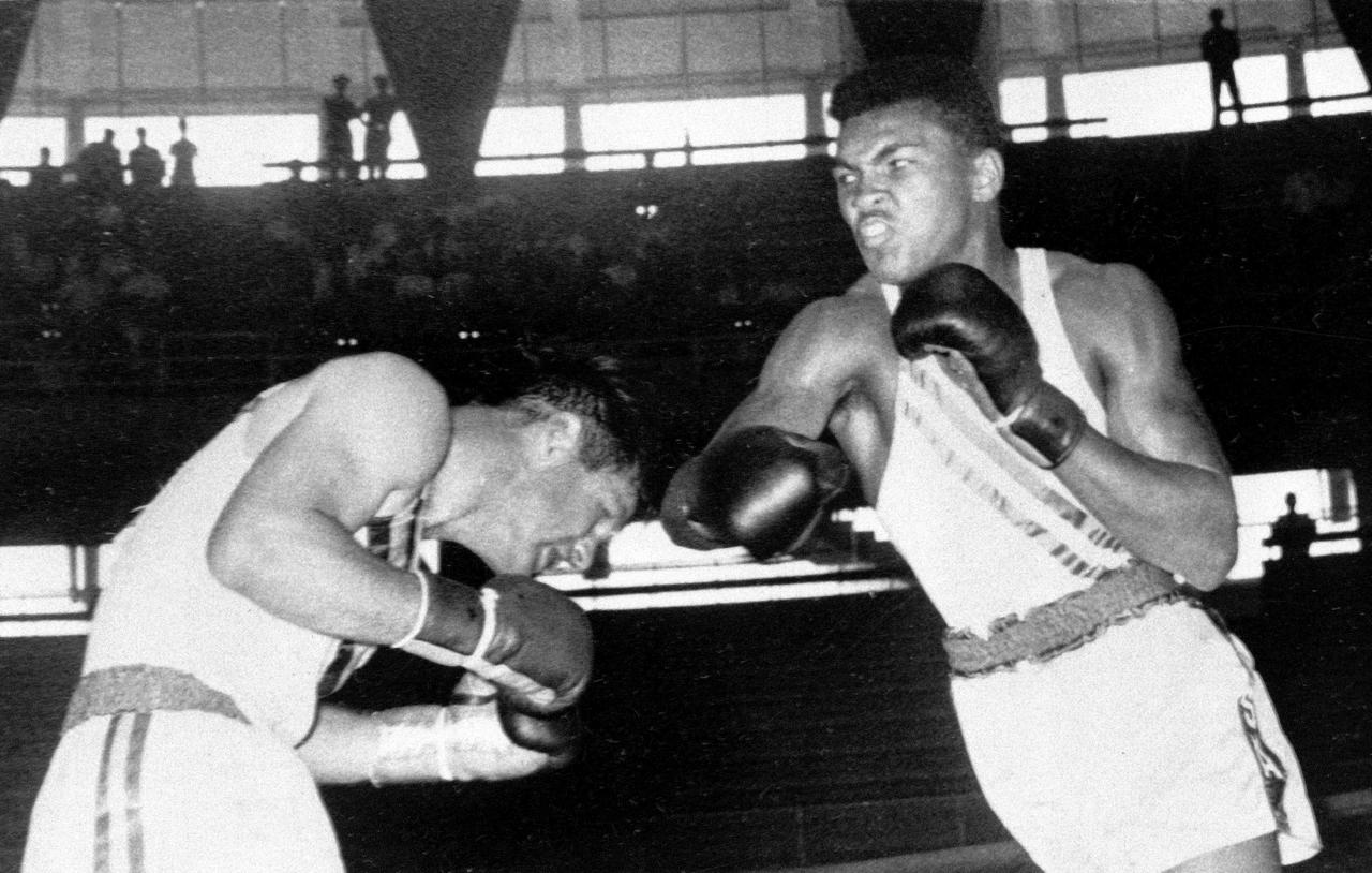 Cassius Clay, 18-year-old from Louisville, Ky., throws a right at Tony Madigan of Australia, left, during the light heavyweight boxing semi-finals at the Summer Olympic Games in Rome, Italy, Sept. 3, 1960.  Clay won the bout with all five votes of the judges.  (AP Photo)