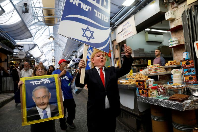 FILE PHOTO: Likud party supporters, one wearing a mask depicting U.S. President Donald Trump, hold election campaign placards, one depicting Israeli Prime Minister Benjamin Netanyahu, as they walk past stalls in Mahane Yehuda Market in Jerusalem