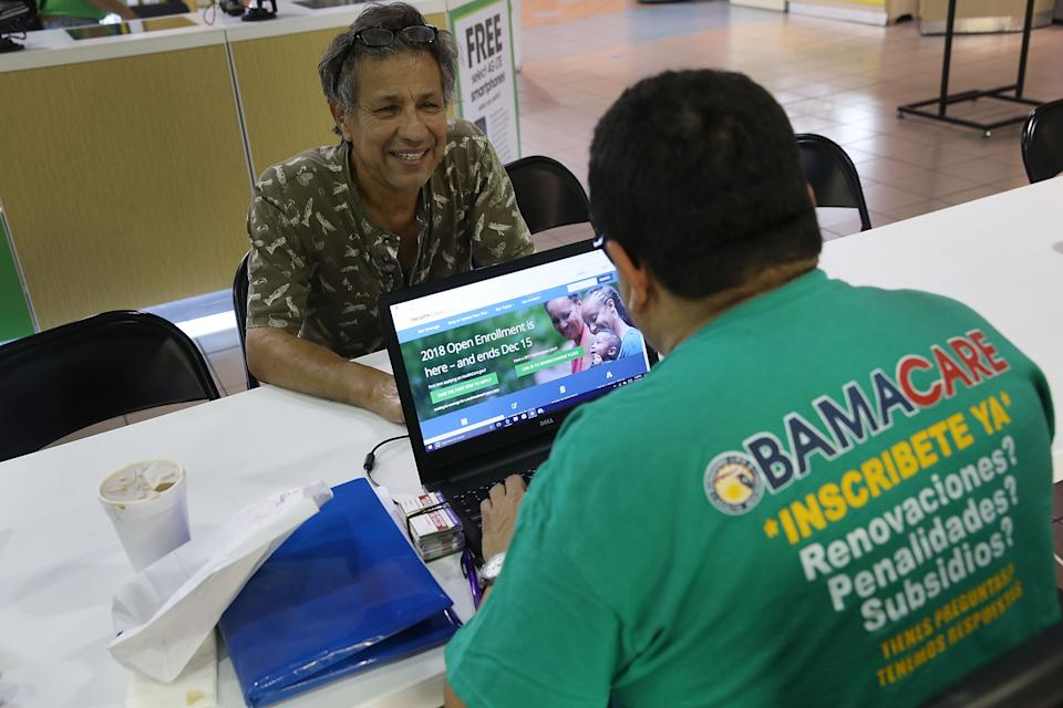 MIAMI, FL - NOVEMBER 01: Rudy Figueroa (R), an insurance agent from Sunshine Life and Health Advisors, speaks with Marvin Mojica as he shops for insurance under the Affordable Care Act at a store setup in the Mall of Americas  on November 1, 2017 in Miami, Florida. The open enrollment period to sign up for a health plan under the Affordable Care Act started today and runs until Dec. 15.  (Photo by Joe Raedle/Getty Images)
