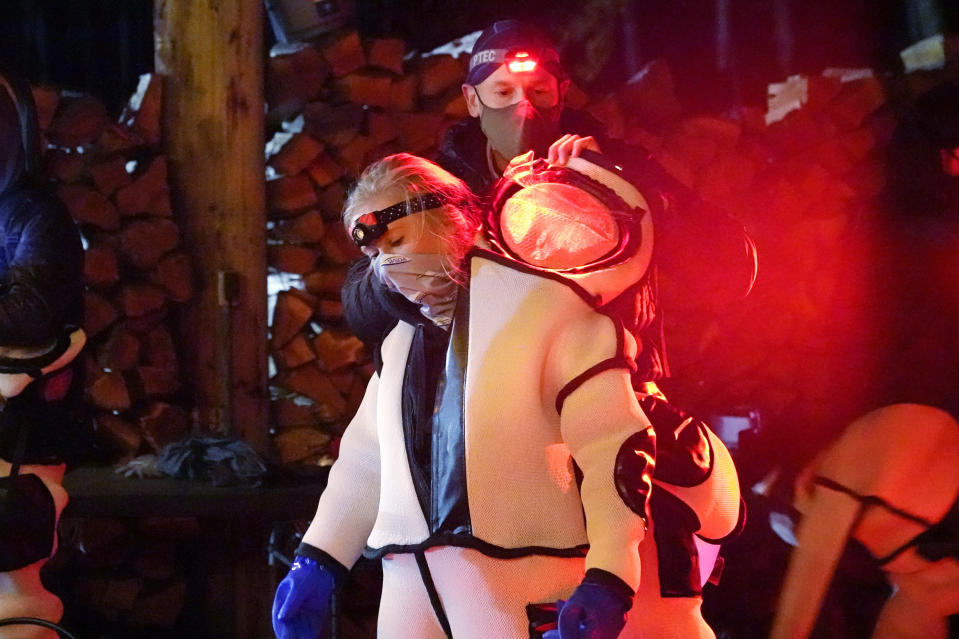 Washington State Department of Agriculture Outreach & Education Specialist Cassie Cichorz is assisted in putting on a protective suite before assisting to eradicate a nest of Asian giant hornets Saturday, Oct. 24, 2020, in Blaine, Wash. Scientists in Washington state discovered the first nest earlier in the week of so-called murder hornets in the United States and plan to wipe it out Saturday to protect native honeybees, officials said. Workers with the state Agriculture Department spent weeks searching, trapping and using dental floss to tie tracking devices to Asian giant hornets, which can deliver painful stings to people and spit venom but are the biggest threat to honeybees that farmers depend on to pollinate crops. (AP Photo/Elaine Thompson)