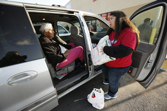 "Volunteer Susan Hartley, right, a schoolteacher, delivers groceries from a shopping list to Anna Woods, 85, at the Grocery Outlet Bargain Market in Altadena. <span class=""copyright"">(Al Seib/Los Angeles Times)</span>"