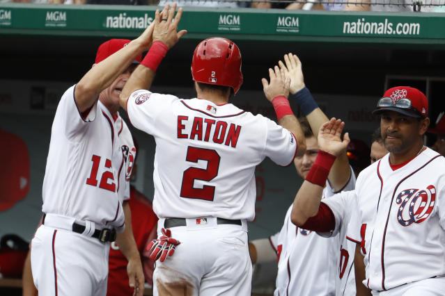 Washington Nationals' Adam Eaton (2) is congratulated by bench coach Chip Hale (12), shortstop Trea Turner (7) and manager Dave Martinez (4) as he returns to the dugout after scoring in the third inning of a baseball game against the Miami Marlins, Sunday, May 26, 2019, in Washington. Eaton and Anthony Rendon (6) scored after Howie Kendrick (47) singled to center. (AP Photo/Jacquelyn Martin)