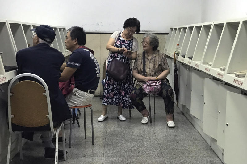 Women chat as investors monitor stock prices at a brokerage house in Beijing, Monday, July 16, 2018. Shares edged lower in Asia early Monday after China reported lackluster growth data in line with expectations. (AP Photo/Andy Wong)