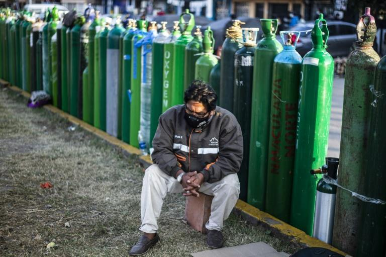People brave the night chill, taking cover in small tents, under blankets or sheets of cardboard outside Criogas, a small oxygen factory in the port city of El Callao near the capital Lima