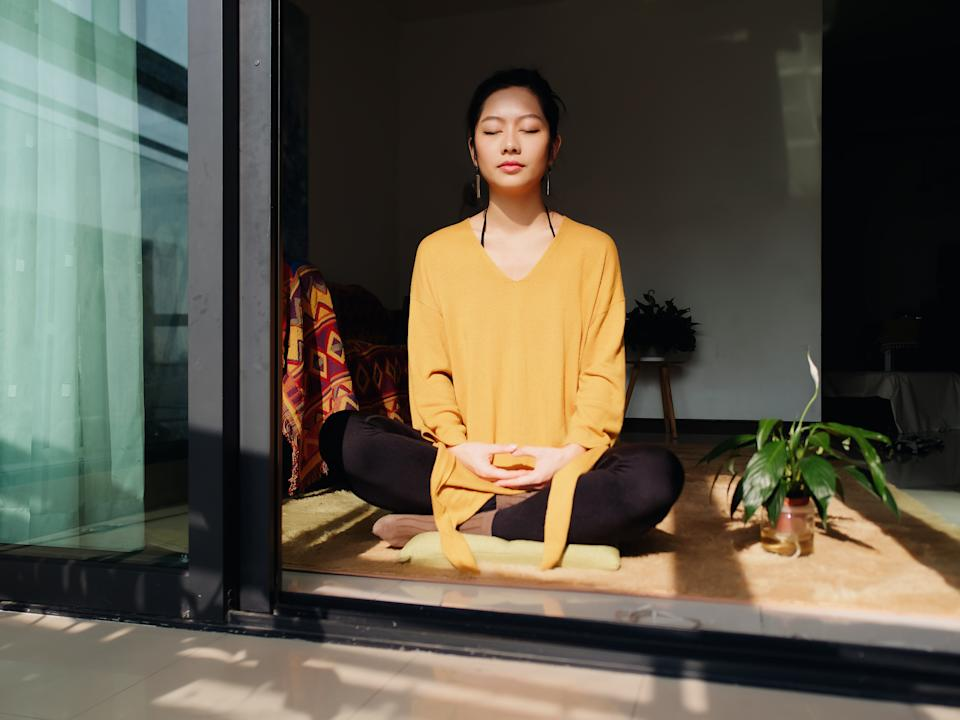 Pretty Chinese young woman meditating at home, sitting on floor with furry cushion in sun light, exercise, Lotus pose, prayer position, namaste, working out, Feeling peace and wellness concept.