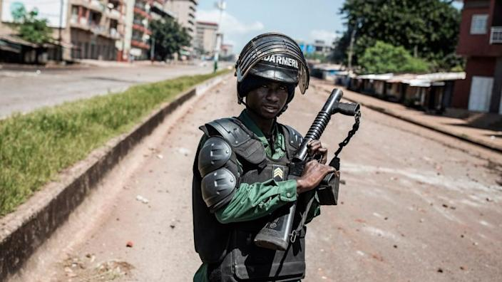 A Police officer is seen in front of protesters, as they continue to throw stones and block roads during mass protests after preliminary results were released in Conakry on October 23, 2020.