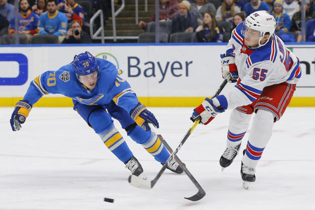 New York Rangers' Ryan Lindgren, right, passes the puck as he is pressured by St. Louis Blues' Oskar Sundqvist, of Sweden, during the second period of an NHL hockey game Saturday, Jan. 11, 2020, in St. Louis. (AP Photo/Billy Hurst)