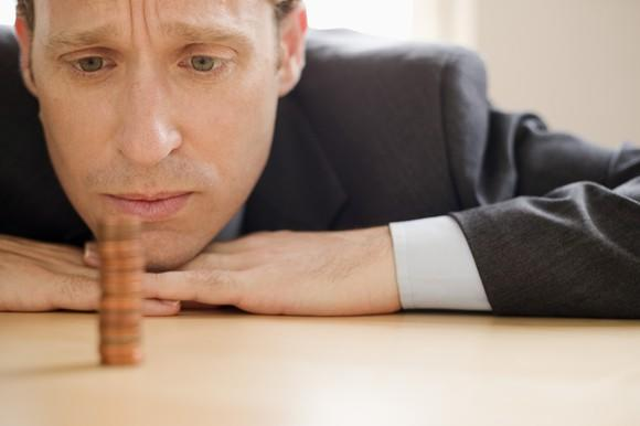 A depressed man in a suit staring at a single stack of pennies on a table.