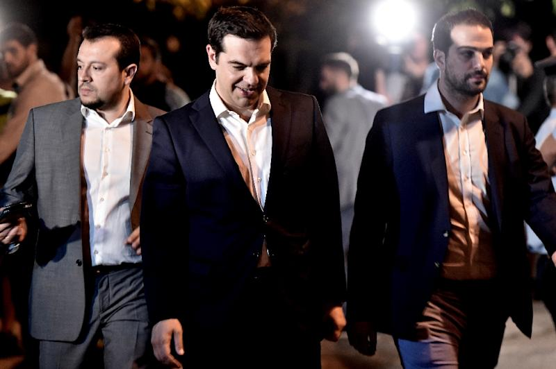 Greek Prime Minister Alexis Tsipras (C) heads to a meeting with the president in Athens on July 5, 2015 after voters overwhelmingly rejected international creditors' tough bailout terms (AFP Photo/Aris Messinis)