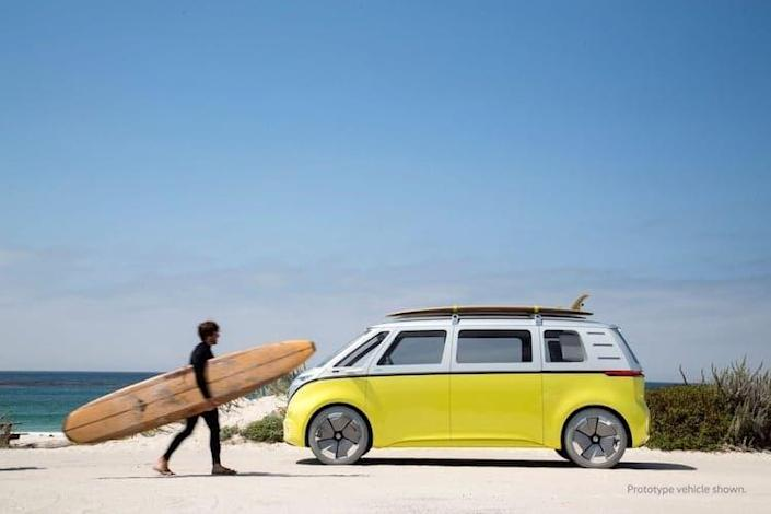 Surfer runs to put his board back on the roof of his fully electric Volkswagen I.D. Buzz.