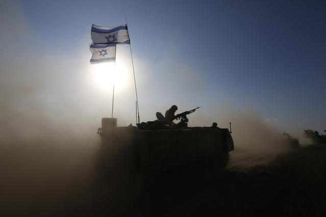 An Israeli soldier rides an armoured personnel carrier (APC) towards a staging area near the border with the Gaza Strip August 4, 2014. Palestinians accused Israel of breaking its own ceasefire on Monday by launching a bomb attack on a refugee camp in Gaza City that killed an eight-year-old girl and wounded 29 other people. An Israeli military spokeswoman said she was checking the report. REUTERS/Baz Ratner (ISRAEL - Tags: POLITICS CIVIL UNREST MILITARY CONFLICT TPX IMAGES OF THE DAY)