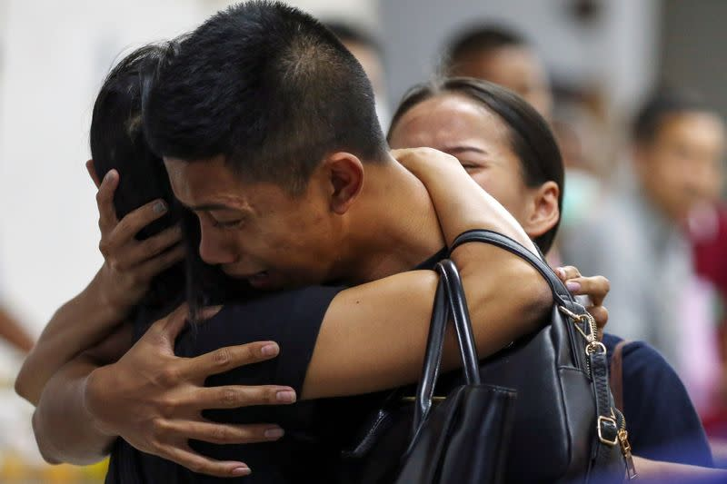 Son and daughter of Captain Siriwiwat Sangprasita, a victim of a gun battle involving a Thai soldier on a shooting rampage, cry after seeing his dead body at a hospital in Nakhon Ratchasima