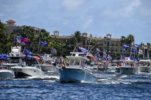 """Boats in the """"Trumptilla"""" -- a flotilla of Donald Trump supporters -- wave American flags, Trump 2020 flags and MAGA flags for the US president's birthday on June 14, 2020 in Fort Lauderdale, Florida"""