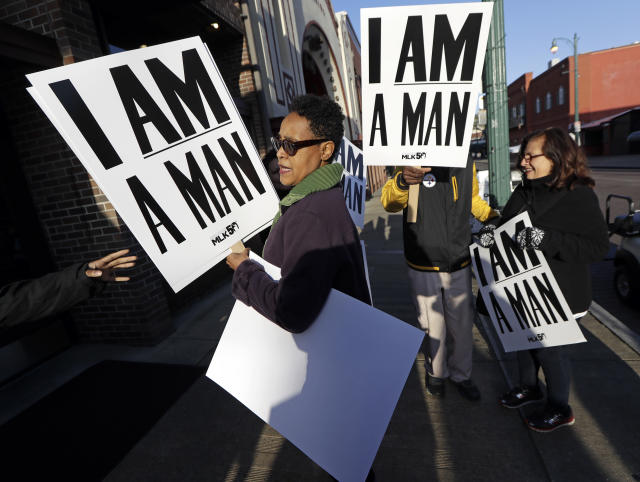 <p>Dwania Kyles hands out signs resembling the signs carried by striking sanitation workers in 1968 as people gather for an event commemorating the 50th anniversary of the assassination of the Rev. Martin Luther King Jr. on Wednesday, April 4, 2018, in Memphis, Tenn. (Photo: Mark Humphrey/AP) </p>