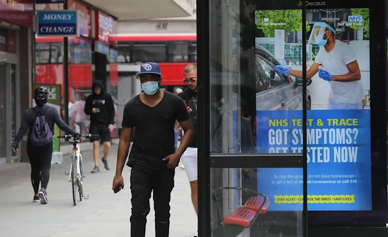 A pedestrian walks past a screen on a bus stop displaying a NHS notice on test and trace on Oxford Street, London, as non-essential shops in England open their doors to customers for the first time since coronavirus lockdown restrictions were imposed in March. Picture date: Monday June 15, 2020.