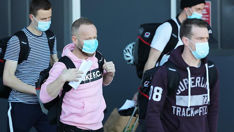 AFL umpires and players, pictured here arriving in Perth before entering a quarantine hub.