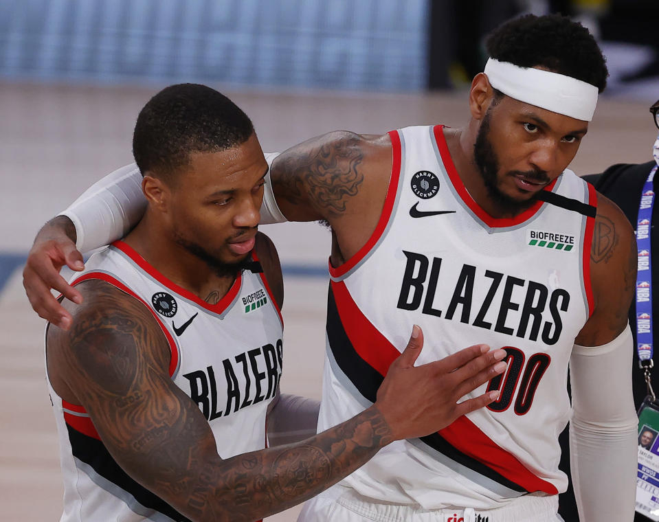 Portland Trail Blazers' Carmelo Anthony, right, and Damian Lillard celebrate the team's win over the Philadelphia 76ers in an NBA basketball game Sunday, Aug. 9, 2020, in Lake Buena Vista, Fla. (Kevin C. Cox/Pool Photo via AP)