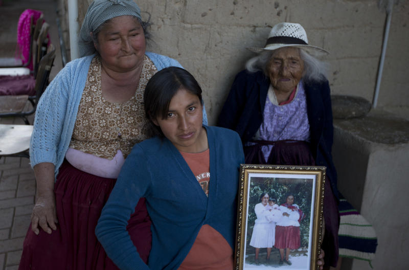 In this Aug. 23, 2018 photo, 117-year-old Julia Flores Colque Julia Flores Colque, behind right, poses for a photo with her grandniece Agustina Berna, left, and her great-grandniece Rosa Lucas at their home in Sacaba, Bolivia. In her long life, Julia has witnessed two world wars, revolutions in her native Bolivia and the transformation of her rural town of Sacaba from 3,000 people to a bustling city of more than 175,000 people in just five decades. (AP Photo/Juan Karita)