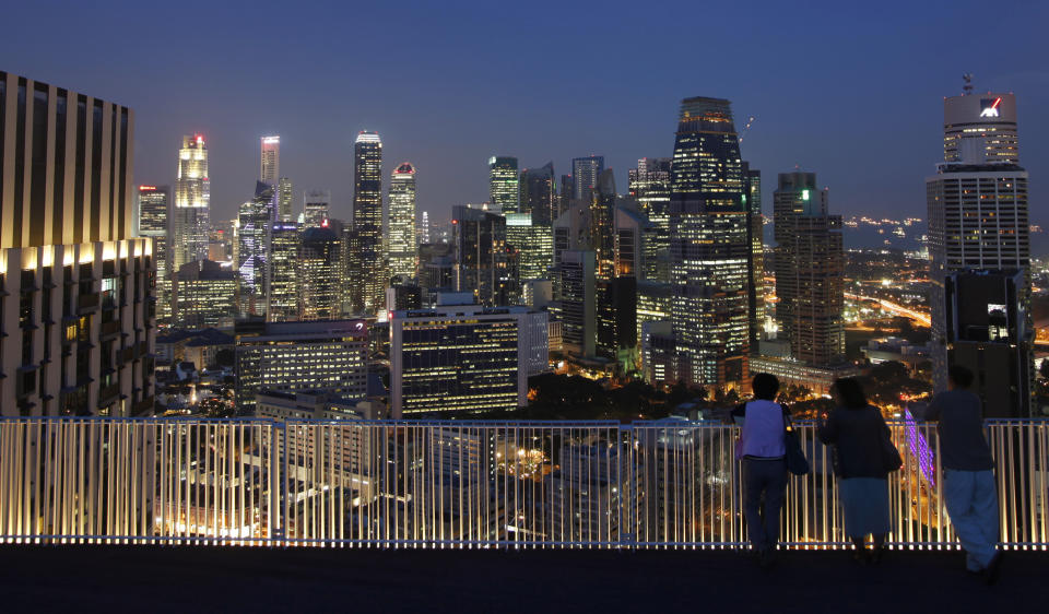 People look at the skyline of the central business district from the Skybridge of The Pinnacles at Duxton public housing estate in Singapore April 25, 2013. Banks in Singapore are urgently scrutinising their account holders as an imminent deadline on stricter tax evasion measures forces them to decide whether to send some of their wealthiest clients packing. The Southeast Asian city-state has grown into the world's fourth-biggest offshore financial centre but, with U.S. and European regulators on the hunt for tax cheats, the government is clamping down to forestall the kind of onslaught from foreign authorities that is now hitting Switzerland's banks. Before July 1, all financial institutions in Singapore must identify accounts they strongly suspect hold proceeds of fraudulent or wilful tax evasion and, where necessary, close them. After that, handling the proceeds of tax crimes will be a criminal offence under changes to the city-state's anti-money laundering law. Picture taken April 25, 2013. REUTERS/Edgar Su (SINGAPORE - Tags: CITYSCAPE BUSINESS)