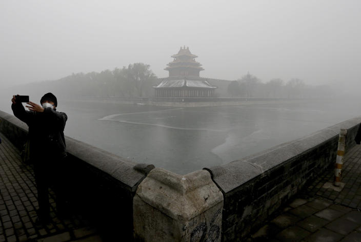 FILE - In this Tuesday, Dec. 1, 2015 file photo, a man wearing a mask to protect himself from pollutants takes a selfie near the Turret of the Forbidden City on a heavily polluted day in Beijing. The World Health Organization said Wednesday Sept. 22, 2021, the negative health impacts of poor air quality kick in at lower levels than it previously thought, announcing revisions to its guidelines on air quality that set a higher bar for policymakers in a world where 90 percent of people already live in areas with one particularly harmful type of pollutant. (AP Photo/Andy Wong, File)